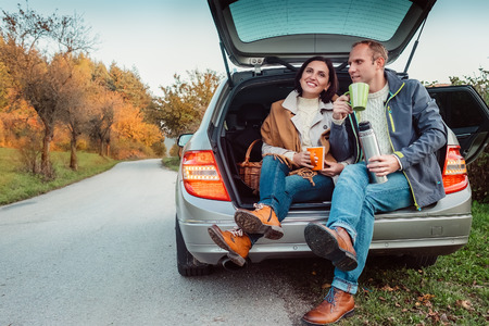 Tea party in car trunk - loving couple drinks hot tea from thermos flask sitting in car trunk Foto de archivo