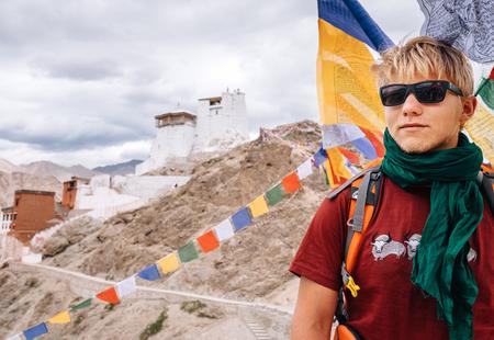 Young man tourist portrait near the tibetan monactety in mountain