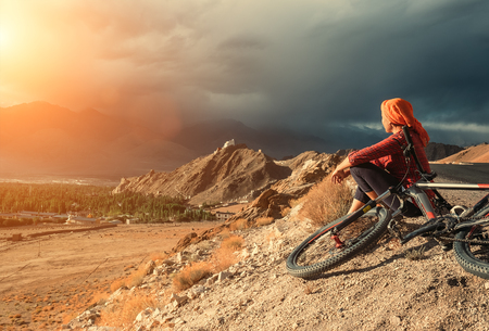 Woman bicycle traveler looking to Ladakh mountain range, India