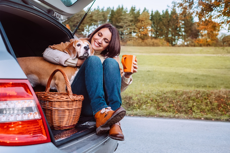 Woman with her dog have a tea time during their autumn auto travel photo