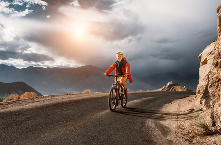 Young man tourist rides bike on road in Himalaya Mountain. Storm sky background