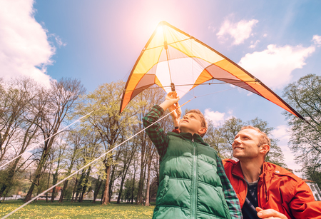 Father with son start to fly a kite photo