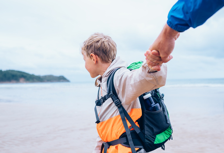 Boy takes his father hands. Active family vacation concept image photo