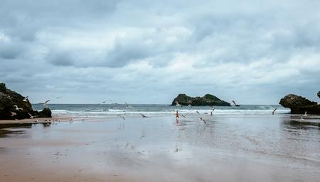 Tiny figurine little boy running on deserted sea coast with flying seagulls