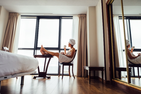Woman relaxes with cup of tea near the panorama window in luxury hotel room photo