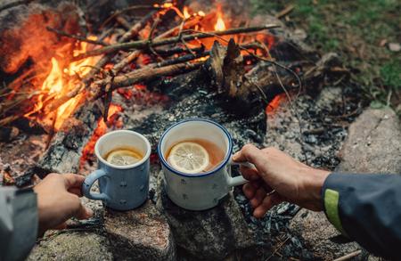 Theepartij in de buurt van kampvuur. Paar drink thee met citroen Stockfoto
