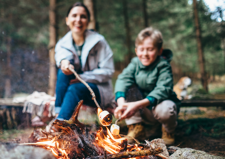 Mother and son cook marshmallow candies on the campfire photo