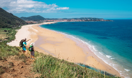 家族のアクティブな休暇: 大西洋の海辺に観光客が息子母