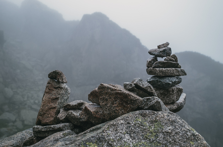 Human-made pile of stones - cairn as way marker in foggy mountain