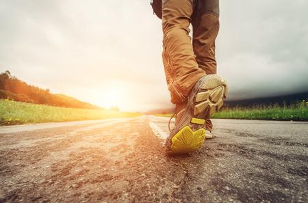 Chiuda sui piedi del viaggiatore del piede sulla strada asfaltata nel tempo del tramonto
