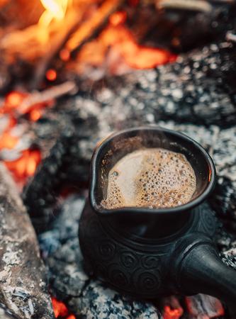 Boil coffee on turkish cezva on campfire coals