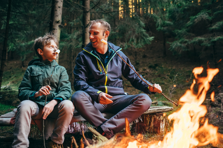 Father and son roast marshmallow candies on the campfire in forest Фото со стока