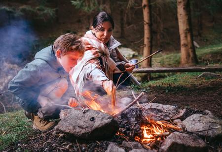 Mother with son make campfire Фото со стока