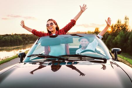 Podróż samochodem - szczęśliwa para zakochanych iść samochodem kabrioletu w czasie zachodu słońca