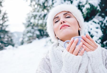De vrouw in bont witte hoed geniet van met warme drank Stockfoto