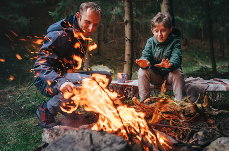 Father with son makes campfire in forest