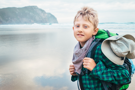 Boy traveler with backpack on ocean beach at the erly morning