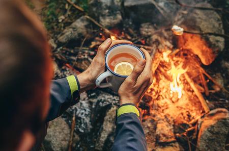 Traveler hand with big mug of hot tea near campfire