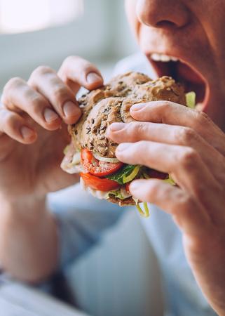 De hongerige man eet een grote sandwich