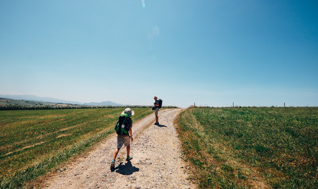 Father and son backpacker travelers walk on countryside road across field