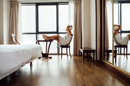 Femme après douche se détendre dans la chambre d & # 39 ; hôtel près de la fenêtre de latone Banque d'images - 88276469
