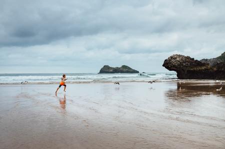 Boy runs on the ocean beach after rain Stock Photo