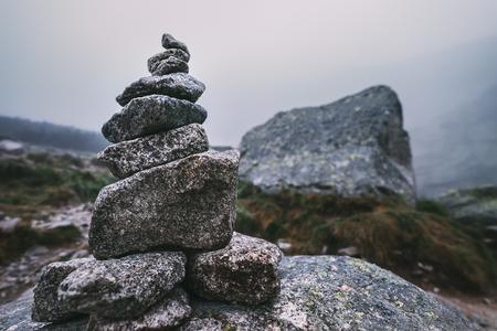 Door de mens veroorzaakte stapel stenen - cairn als wegmarkering in mistige berg
