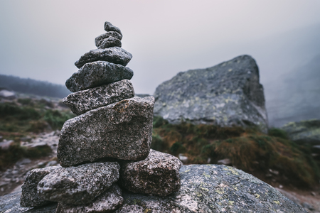 Human-made pile of stones - cairn as way marker in foggy mountain Reklamní fotografie - 88276473