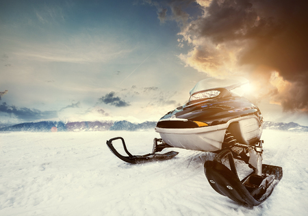 Snowmachine on the mountain lake frozen surface with thunderstorm clouds on the background Stock Photo