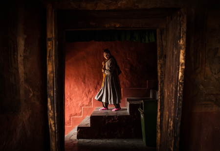 Thikse Monastery in Ladakh, India - AUGUST 20: Tibetan monk woman goes down the stairs in Thiksey Monastery on August 20, 2016 in Thiksey village in Ladakh, India