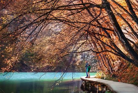 Father and son walk near the beautiful mountain lake at sanny autumn day
