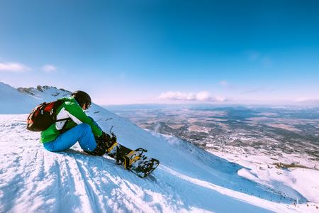 스노우 보더는 스노우 힐 꼭대기에 앉아 있습니다.