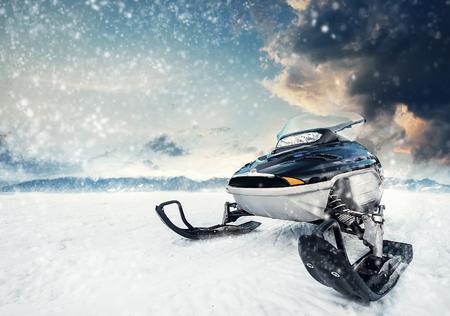 背景に雷雨の雲と山湖の凍った地表の Snowmachine