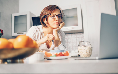 Woman prepare breakfast and watch laptop on kitchen