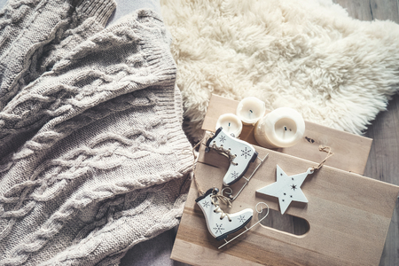 Big knitted sweater, candles and christmas decoration cozy living mood background 스톡 콘텐츠