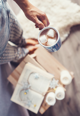 Woman hand with cup of hot chocolate: cozy home interior, Christmas time mood