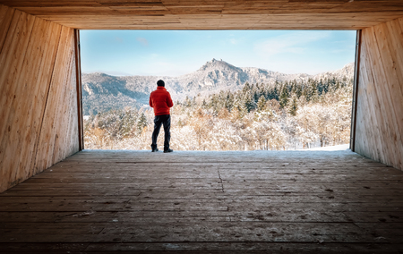 Man stays in big wooden hangar and looks on snowy mountains Stock Photo
