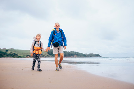 Traveling with child: father and son walk with backpack on sandy ocean beach, rainy day