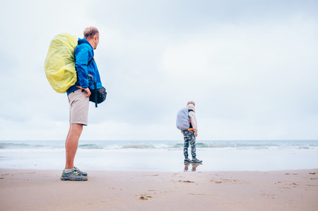 Backpacker travelers father and son  stay on ocean desret beach in rainy day