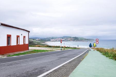 Two backpacker travelers walk on road in city on seaside