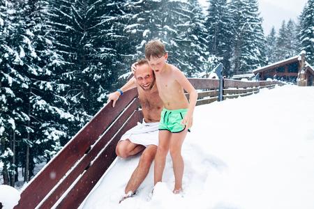 父と息子は、熱いサウナ後雪でリフレッシュします。