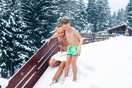 Father and son refresh in snow after hot sauna 免版税图像 - 91948515