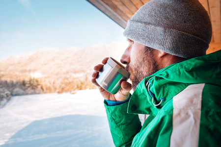 Man with cup of hot drink wqrms on open winter air Stock fotó