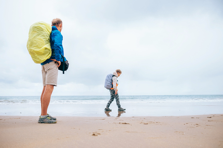 Traveling with child: father and son enjoyed empty ocean beach Stock Photo