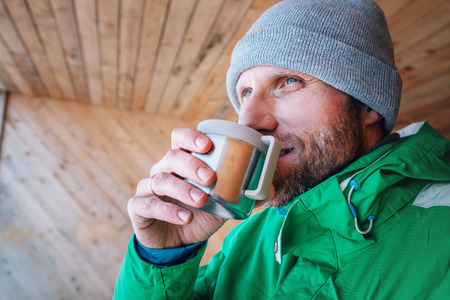 Man with cup of hot drink warms on open winter air