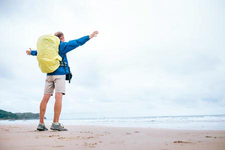 Backpacker traveler enjoy with ocean energy on the empty beach in rainy day