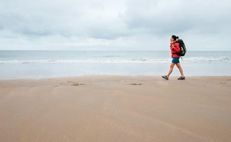 Vrouw reiziger lopen op lege oceaan strand in regenachtige dag