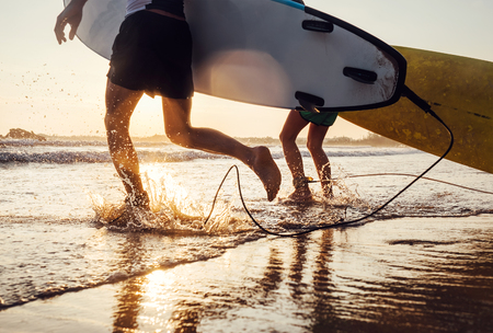 Son and father surfers run in ocean waves with long boards. Close up splashes and legs image Archivio Fotografico