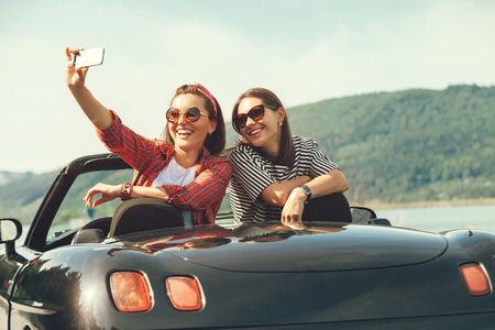 Two female freinds take a selfie photo in cabriolrt car during their summer voyage Foto de archivo