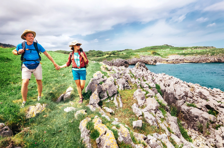 Couple backpacker travelers walk on ocean rocky coast. Asturias. Spain Stock Photo